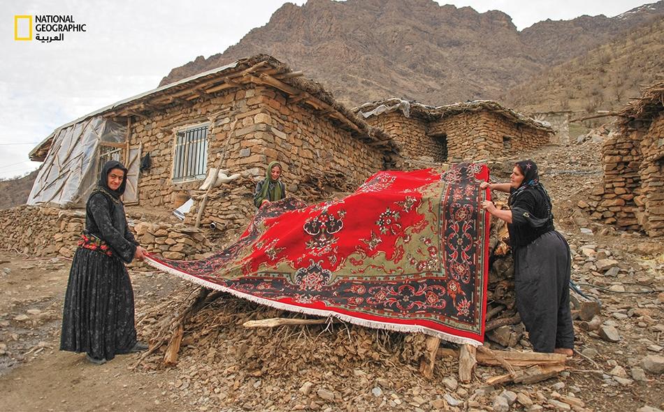 """مع اقتراب فصل الشتاء تقوم نسوة من قرية """"سوني"""" الحدودية بتهوية السجاد تمهيداً لفرشه فوق أرضية منازلهن الحجرية البسيطة."""