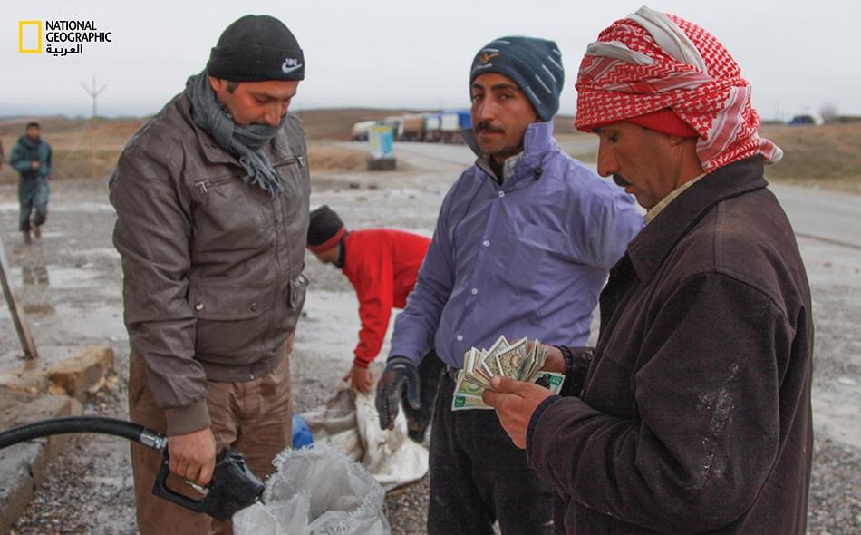 مهربون يملؤون عبواتهم بالوقود من إحدى الشاحنات بالقرب من الحدود قبل بدء رحلة العبور.
