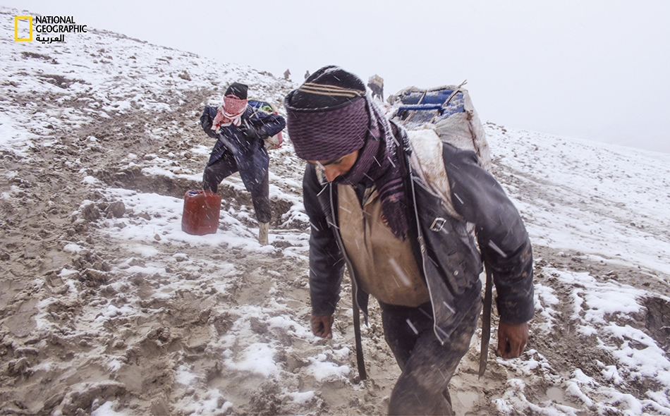 """مهربان يأخذان قسطاً من الراحة قبيل بدء عاصفة ثلجية. ينقل المهربون المعروفون باسم """"كولبار"""" على ظهورهم، عبوات من الوقود المكرر، سعة الواحدة منها حوالى 30 لتراً إلى مدينة """"المالكية"""" في محافظة الحسكة السورية."""