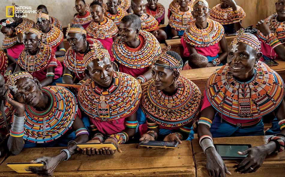 """رغبة تعليم الأبناء مبادئ الحاسوب تدفع نساء قبيلة """"سامبورو"""" للحضور إلى فصل دراسي في مستوطنة بشمال نيروبي. وهنّ يتعلّمن استخدام الحواسيب اللوحية -المصمَّمة لتحمّل الاستخدام المكثف- الموصولة بالإنترنت عبر قمر صناعي، والمحمّلة مسبقاً ببرامج تعليمية."""