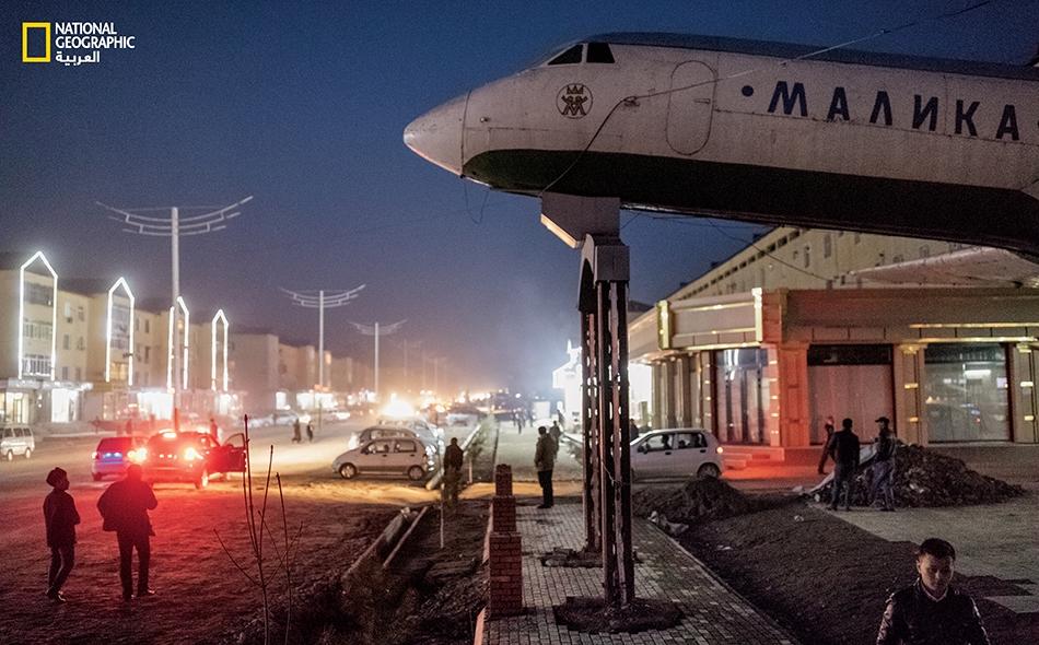 """طائرة نفّاثة من الاتحاد السوفيتي تَلوح بالقرب من مقهى بمدينة """"أنديجان"""" في أوزبكستان، التي كانت تُعَدُّ محطة أساسية على طريق الحرير القديمة."""