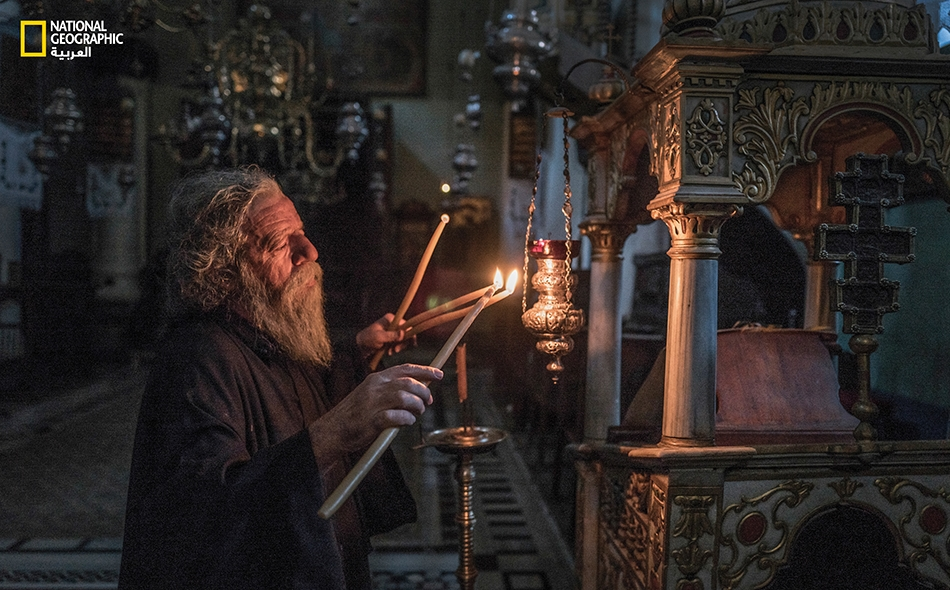 """""""ياني"""" أحد أشهر رهبان الدير والحافظ الوحيد عن ظهر قلب للتوراة والإنجيل، ينير القاعة الرئيسة للكنيسة الكبرى بالشموع، قبيل الصلاة، في تقليد قديم يعود إلى مئات السنين."""