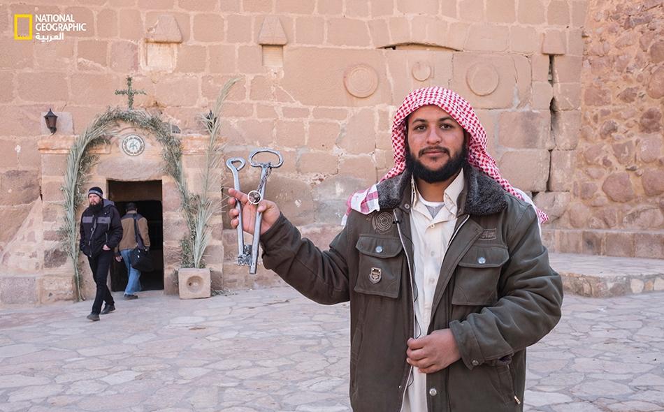 """حارس الدير """"رمضان موسى""""، يحمل في يده مفاتيح الباب الرئيس للمجمّع الديني."""