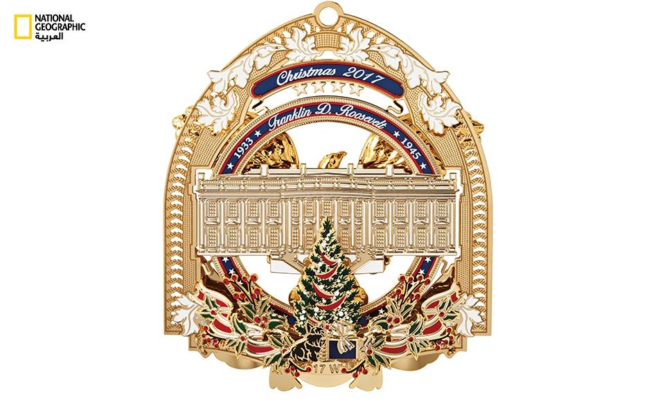 """صُنعت القطعة أعلاه لتكريم الرئيس فرانكلين روزفلت، وقد جُعلت في تصميم مستوحى من المذياع القديم الذي كان يُوضع على أسطح المناضد. ويجلس """"فالا""""، كلب روزفلت المفضل، مع الهدايا بالقرب من شجرة عيد الميلاد."""