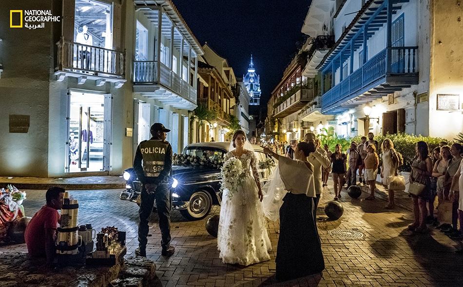 """أُناسٌ من المارّة يشاهدون وصول حفل زفاف سيُقام في """"كنيسة سان بيدرو كلافر"""" في مدينة """"كارتخينا"""" التاريخية. تعد المعالم الاستعمارية الإسبانية للمدينة نعمة للسياحة بالبلد، والتي تقول عنها الحكومة الكولومبية إنها نمت بنسبة 250 بالمئة منذ عام 2006."""