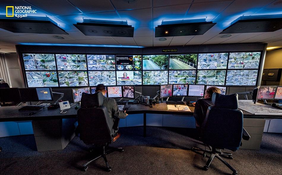 """عاملا تشغيل نظام للدوائر التلفزيونية المغلقة (CCTV) يراقبان شاشات غرفة مراقبة منطقة """"إزلينغتون""""، حيث يمكنهما متابعة الصور الواردة من الشبكة واسعة النطاق لكاميرات المنطقة."""