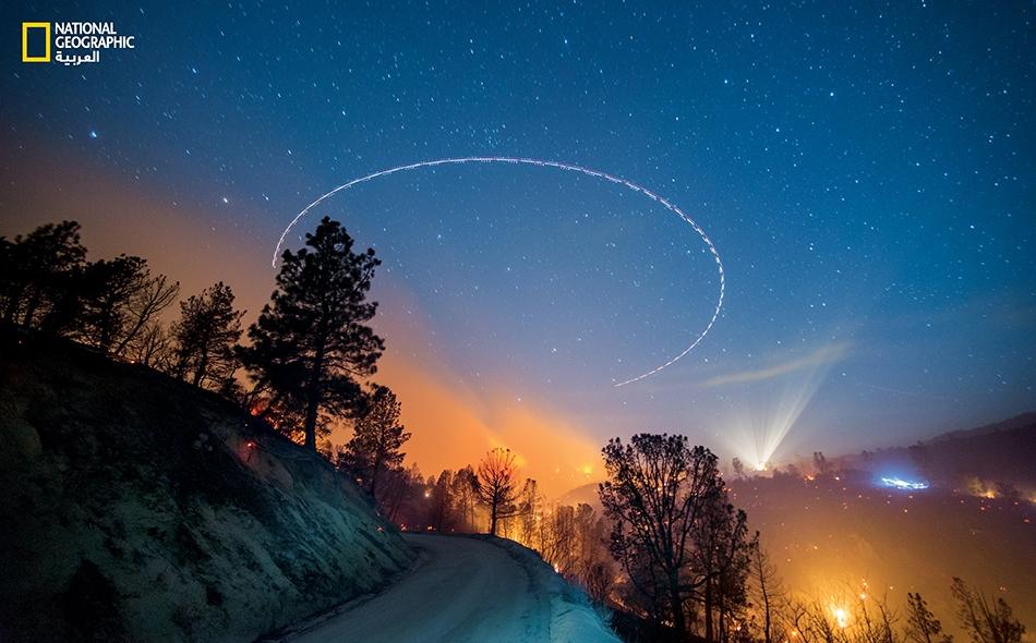"""في هذه الصورة التي أُنتجت بالتعريض الطويل، طائرة تابعة لـ """"دائرة الغابات الأميركية"""" تنعطف فوق حريق هائل على مقربة من بحيرة """"إيزابيلا"""" في """"غابة السِيكويا الوطنية"""" بولاية كاليفورنيا."""
