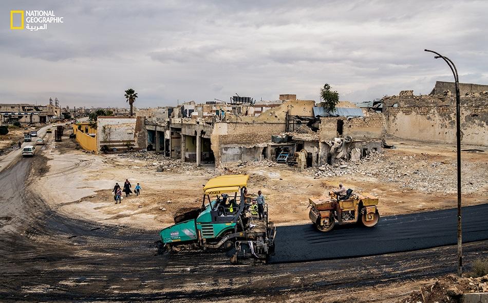 """عمال يشيدون طريقا لتعويض الطريق التي دُمرت قرب المطار الدولي في """"حي كرم الجزماتي"""" شرق مدينة حلب."""