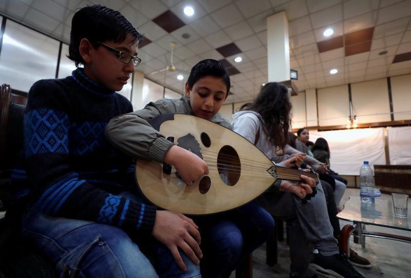 أطفال يعزفون على العود أثناء التدريب على الغناء والإنشاد في حلب يوم 9 فبراير 2018. الصورة: عمر صناديقي – رويترز