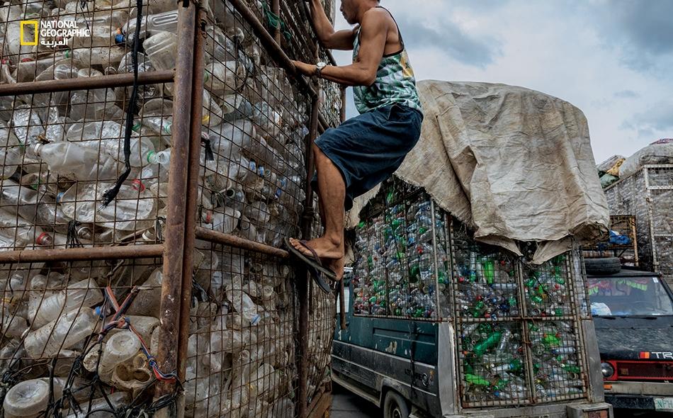 """تتوقف شاحنات مليئة بالقنينات البلاستيكية لدى منشأة لإعادة التدوير في مدينة """"فالينزويلا"""" الفلبينية. كان قد التقط القنينات من شوارع منطقة مانيلا الحضرية الكبرى، نبّاشو قمامة يبيعونها لتجّار خردة يجلبونها إلى هنا. ستُقطّع القنينات وأغطيتها إلى شظايا..."""