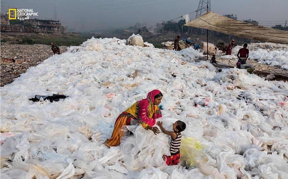 """تغسل """"نورجهان"""" رقائق شفّافة من البلاستيك بمياه نهر """"بوريغانغا"""" في مدينة داكا -عاصمة بنغلادش- ثم تنشرها لتجفّ، مقلّبةً إياها على نحوٍ دوريّ ومعتنيةً بابنها """"مومو"""". في النهاية سيباع البلاستيك لجهة تعيد تدويره. وللعلم فإن أقل من خُمس المواد البلاستيكية..."""