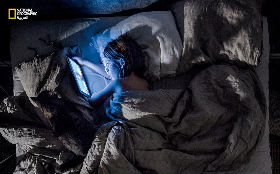 """يبلغ """"ويل وينمان"""" -ابن المصور """"ماغنوس وينمان""""- سبعة أعوام، وهو يشاهد الرسوم المتحركة على جهاز """"آي باد"""" الخاص به؛ فلقد أضحى ذلك طقسا قبل النوم في حياة كثيرين. قد تبدد الإثارةُ النومَ وكذلك تفعل الشاشات ذات الأضواء الخلفية، إذ يمنع الضوءُ ليلا إفرازَ..."""