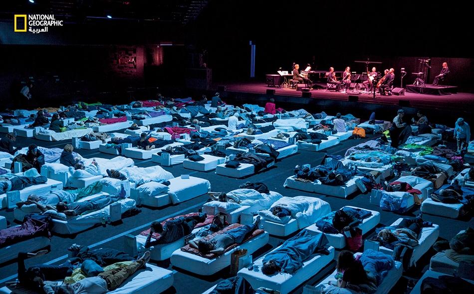 """في مؤسسة """"فيلهارمونية باريس""""، يقود الملحن البريطاني """"ماكس ريكتر"""" جوقة تعزف مقطوعة """"النوم""""، التي تستلهم العلم وتهدف إلى جعل المستمعين يخلدون إلى نوم صحي مجدِّدٍ للنشاط. تدوم المقطوعة ثماني ساعات."""