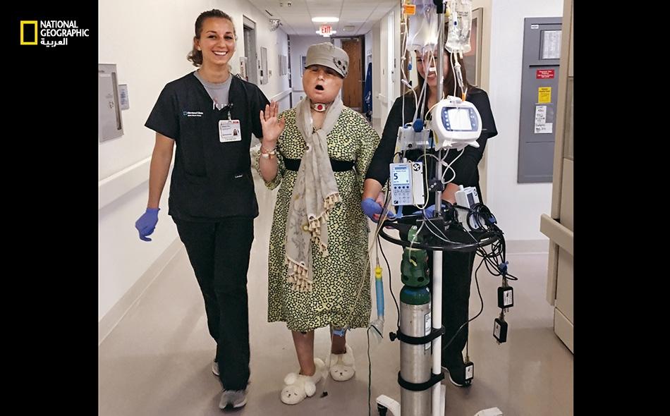 """20 يوما، بعد عملية زرع وجه لكايتي – أثناء إحدى جولات كايتي اليومية في الممرات، تغني الشابة وهي تتدرب مع أخصائية العلاج الطبيعي """" بيكي فانو"""" (يسار) وطالبة العلاج الطبيعي """"نيكول بليس""""."""