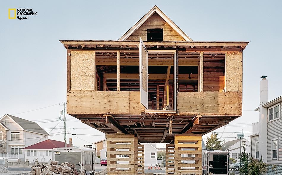"""يُشيَّد هذا البيت في جادَّة """"بيركلي"""" لدى منتزه """"سي سايد"""" بولاية نيوجيرسي، حيث يبدو مستعداً لبدء حياة جديدة. فقد رُفع المنزل فوق قواعد من خشـب رقائقي، بانتظـار أساس نهائي جديد.. ومرتفع عن سطح الأرض."""