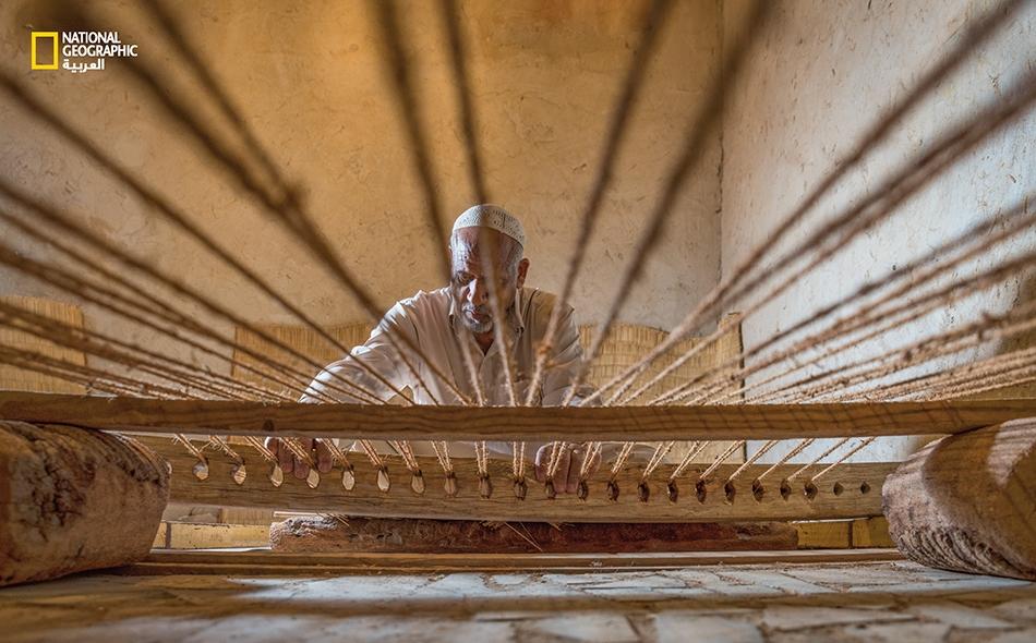 """يجلس """"صالح الحميد"""" وراء النول التقليدي لصنع حصيرة """"المداد""""، التي كانت تستخدم في فرش الأرض قديماً؛ وتصنع عادة من مادة الأسل والليف والحبال."""