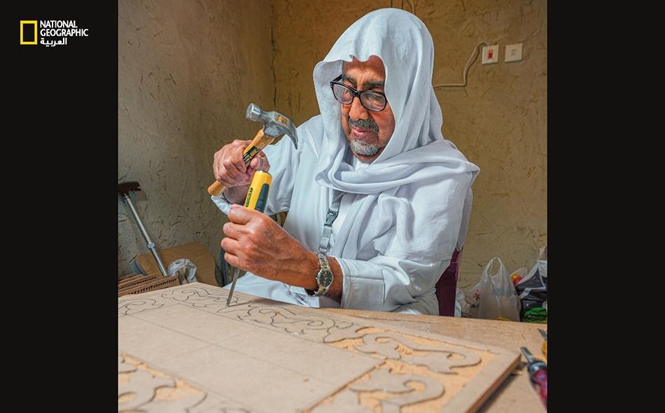 """ينحت """"عبد الله الشبعان"""" على لوح خشبي ما يُعرف بـ""""النقوش الأحسائية"""" التي تجمع بين الأنماط النباتية والهندسية في آن واحد."""