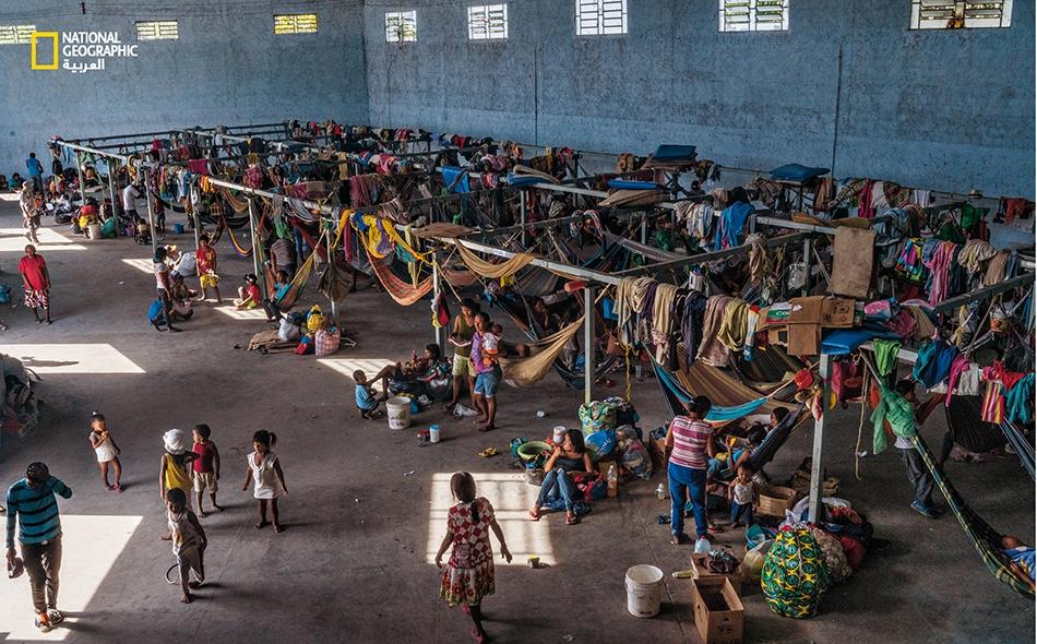 """يعيش زهاء 500 من أفراد قبيلة """"واراو"""" داخل هذا الملجأ الخرساني المجهز بأرجوحات النوم الشبكية والخيام في بلدة """"باسارايما"""" البرازيلية. أدى الزحام وانعدام الشروط الصحية إلى تفشي الأمراض في الملجأ."""