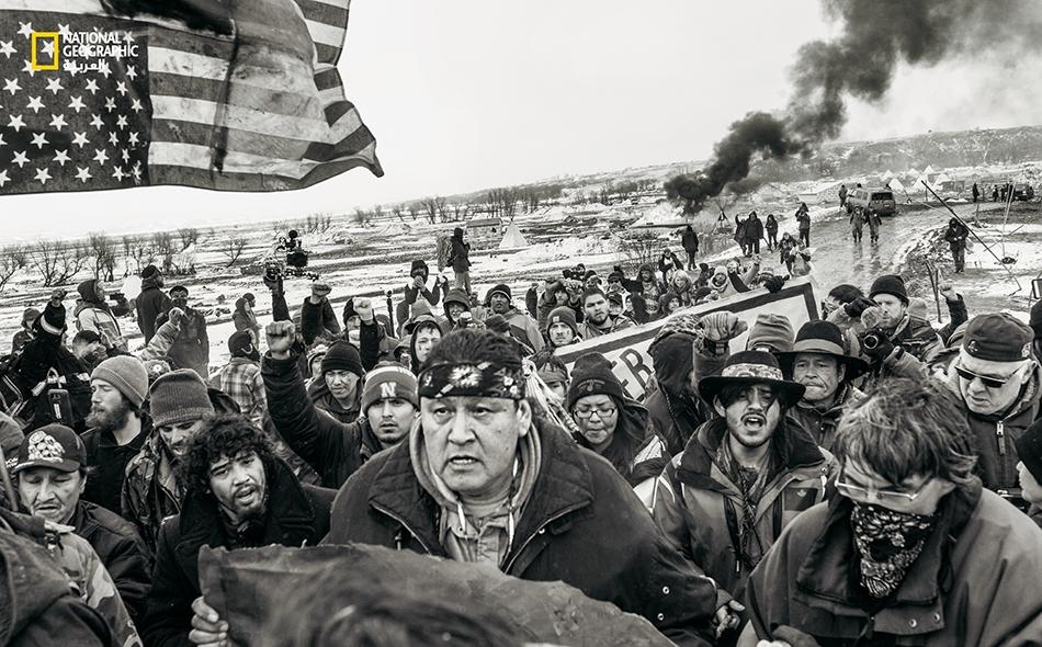 """متظاهرون ضد بناء """"خط أنابيب داكوتا"""" يغادرون مخيم """"أوسيتي ساكوين"""" بالقرب من """"محمية ستاندينغ روك للهنود""""، بعد صدور أمر قانوني بإنشاء الخط في فبراير عام 2017. أسس المصور """"خوسيه ريفاس"""" مشروع """"ستاندينغ سترونغ"""" (الصمود بقوة) الذي يستكشف هوية السكان الأصليين..."""