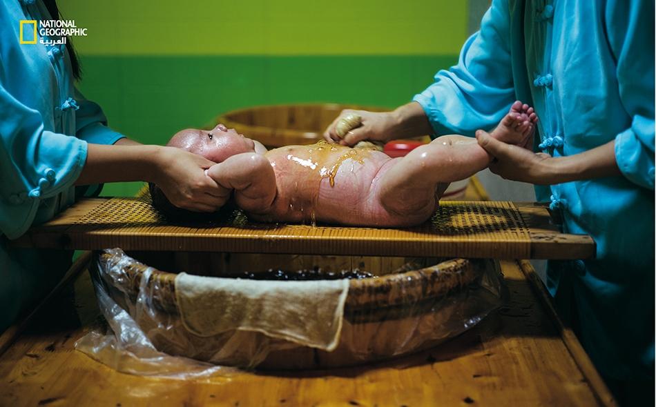 """يُحَمَّمُ """"رن يانيو"""" -ذو الشهرين- في تشينغدو بمحلول عشبي لإزالة السموم من جسمه وتبريده خلال أشهر الصيف الرطبة. يعد هذا الإجراء جزءا من الفلسفة الصينية القاضية بالحفاظ على صحة الجسم وعدم الاقتصار على علاج الأمراض بعد ظهورها."""