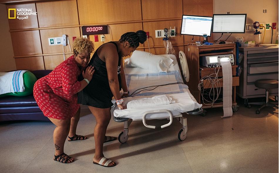 """تقوم """"ديوني ماك دونالد"""" (33 عاماً)، وهي مرشدة صحية مجتمعية متخصصة في فترة ما حول الولادة لدى """"قرية ماماتوتو""""، بمساعدة """"ميغان ستراون"""" (26 عاماً) من خلال ممارسة ضغط مضاد على العَجُز أثناء المخاض في """"مستشفى جورج واشنطن الجامعي"""" بواشنطن العاصمة، خلال شهر..."""