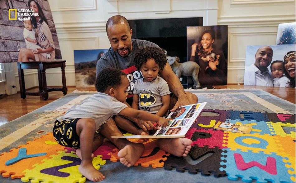 """يلاعب """"تشارلز جونسون الرابع"""" (37 عاماً) وهو محاط بصور زوجته الراحلة """"كيرا جونسون""""، طفليهما، """"تشارلز الخامس"""" (3 أعوام، في حجر والده) ولانغستون (عامان)، في منزله بمدينة أتلانتا في ولاية جورجيا. فقد توفيت كيرا بعد فترة حمل عادي، جراء نزيف داخلي بعد مرور..."""