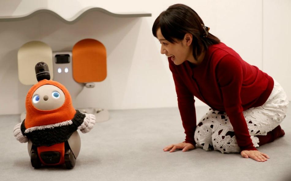 """امرأة تحاور الإنسان الآلي الودود """"لافوت"""" في طوكيو، باليابان. الصورة: كيم كيونج-هون ، رويترز."""