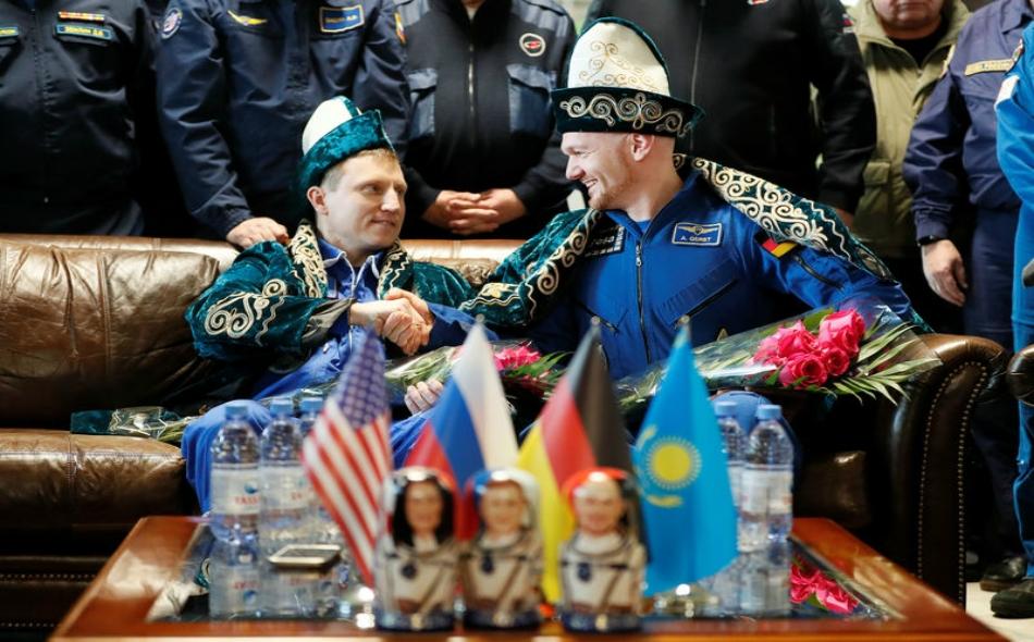 """رائدا الفضاء الألماني """"ألكسندر جيرست"""" والروسي """"سيرجي بروكوبييف"""" يرتديان أزياء كازاخية تقليدية في مؤتمر صحفي بعد عدوتهما من محطة الفضاء الدولية. الصورة: شاميل جوماتوف – رويترز"""