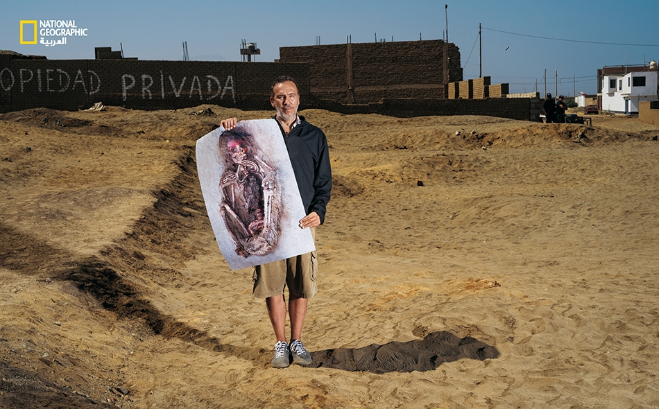 """""""مايكل سبانو""""، صاحب محل لبيع البيتزا بالمنطقة، يحمل صورة لبقايا أحد الضحايا الأولى المكتشفة في موقع """"وانشاكيتو"""". وكان سبانو قد نبَّه عالم الآثار """"غابرييل برييتو"""" إلى وجود عظام ناتئة في رقعة أرض خالية غير بعيد عن منزله، ثم حثّه على التنقيب في الموقع...."""
