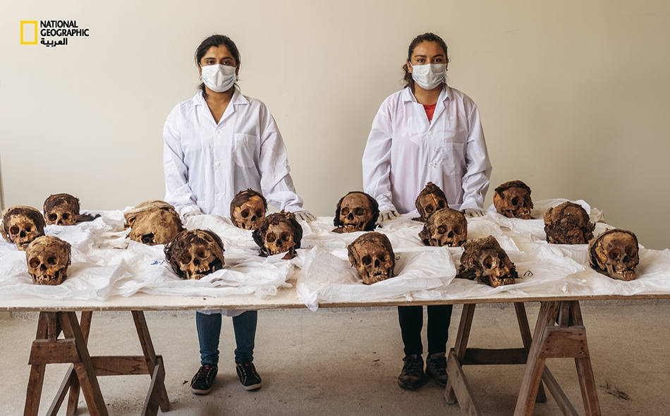 """تستعد طالبتا علم الآثار لدى """"جامعة تريخيّو الوطنية"""" لتنظيف جماجم استُخرجت من المدفن الجماعي لدى """"وانشاكيتو"""" وفهرستِـها. حنّط المناخ الجاف في شمال البيرو كثيراً من بقايا القرابين البشرية بصورة طبيعية، فظلت محفوظة جيداً على نحوٍ غير متوقّع."""