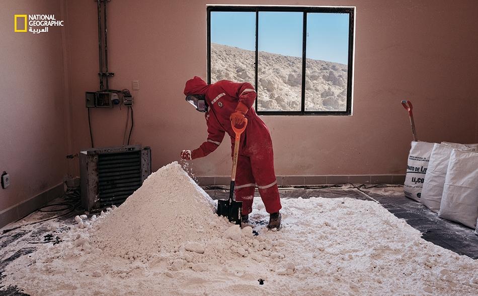 في المصنع التجريبي، يقوم عامل بفحص كربونات الليثيوم ليتأكد من درجة جفافها؛ وهي المرحلة النهائية قبل تعبئة هذه المادة الكيميائية في أكياس ومن ثم توريدها. تضم هذه المنشأة -التي تديرها الدولة- نحو 250 موظفا، يرتدون بذلات حمراء اللون ويعيشون في منازل...