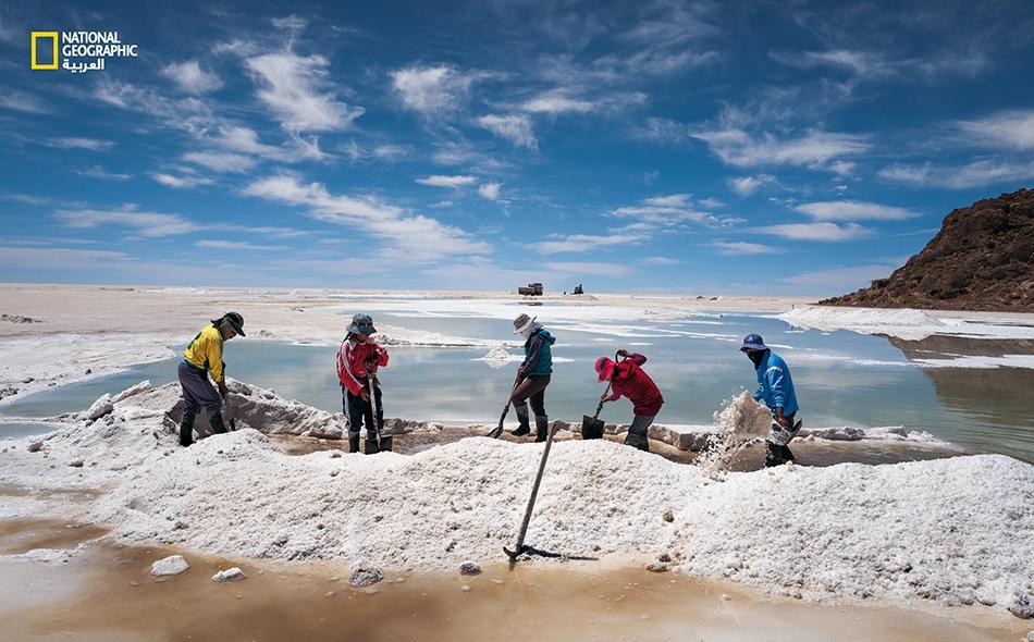 """سكانٌ من شعب """"أيمارا"""" الأصلي يكشطون الملح من على سطح السهل الملحي، """"سالار دي أويوني"""". يتكسب هؤلاء من بيع الملح للمصانع؛ والحال أن الليثيوم الأكثر ربحاً يذوب في المحلول الملحي القابع في أعماق هذا السهل."""