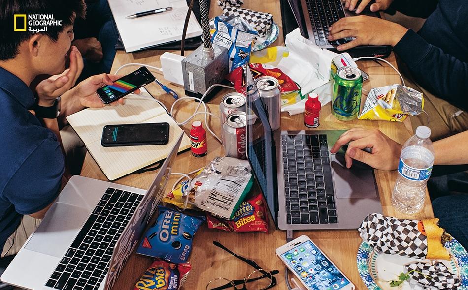 """في هاكاثون (أو بَرمجان) في مدينة """"سانتا كلارا""""، طلاب من """"جامعة نانيانغ التقنية"""" بسنغافورة يبتكرون أفكارا لصنع تطبيق قائم على الواقع المعزز، مخصَّص للمصورين الفوتوغرافيين. أما غذاؤهم فيتألف من: وجبات خفيفة ومشروبات طاقة وصودا خالية من السكر."""