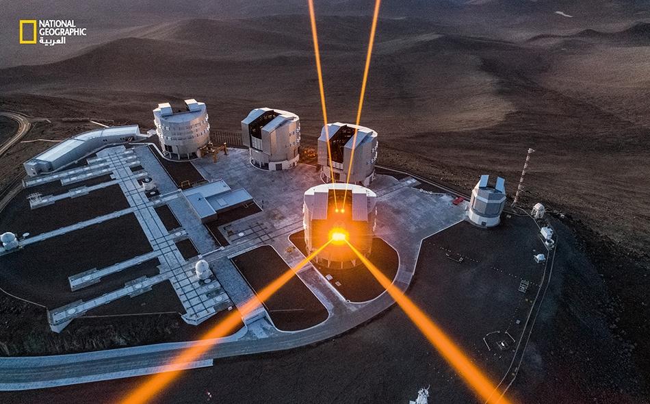 """تندفع أشعة ليزر من مصفوفة """"التلسكوب شديد الضخامة"""" (ELT) التابع لـ """"المرصد الأوروبي الجنوبي""""، والواقع في """"صحراء أتاكاما"""" في تشيلي. تشكل أشعة الليزر هذه نجوماً هادية صناعية تساعد علماء الفلك على تصحيح الانحرافات التي يسببها اضطراب الغلاف الجوي. وهذا..."""