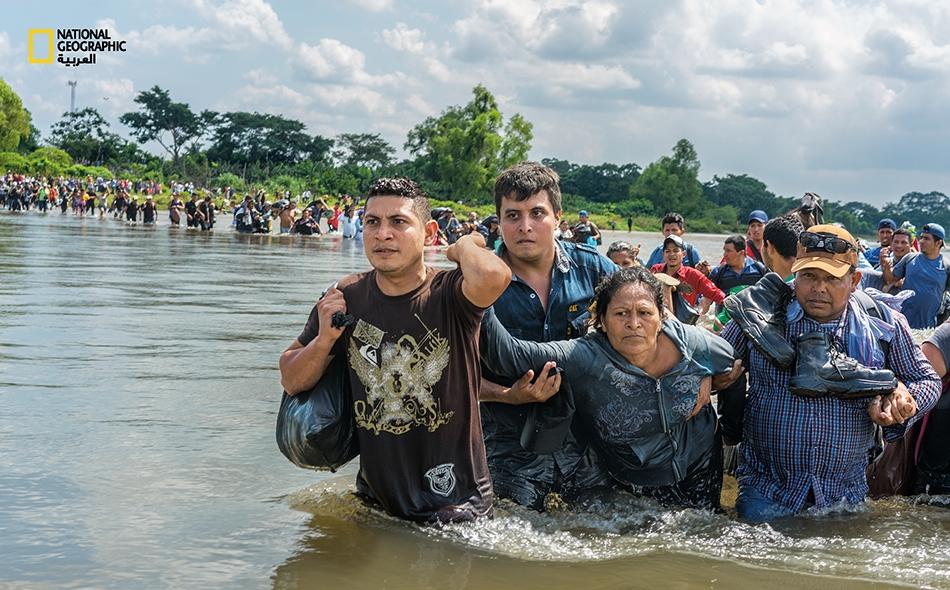 """سلفادوريون يعبرون حدود غواتيمالا إلى المكسيك في نوفمبر 2018. من هنا سيقطعون 3900 كيلومتر أخرى لبلوغ الولايات المتحدة. في ذلك التاريخ، أمر الرئيس """"دونالد ترامب"""" بنقل أزيد من 5000 جندي أميركي إلى الحدود مع المكسيك لردع المهاجرين."""
