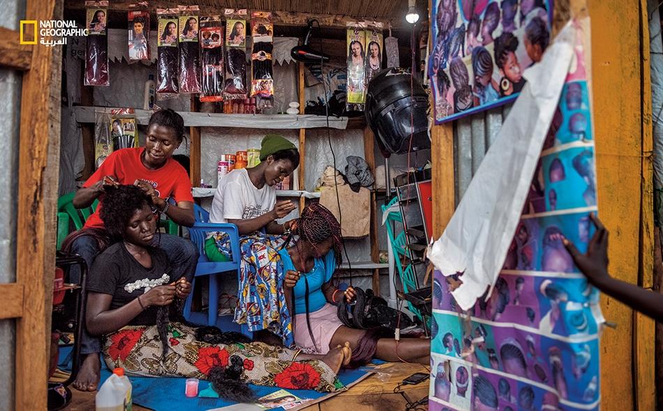 """تعمل """"نايت ماي"""" (يسار) و""""فلورنس ستيما"""" (يمين) -وهما من جنوب السودان- في صالون حلاقة بمخيم """"بيديبيدي"""". تكسب كل واحدة منهما أقل من خمسة دولارات في الأسبوع. وقد ملأت المشروعات التجارية الصغيرة باحات الأسواق، لكن عددًا قليلا من الشركات الخاصة استفاد من..."""