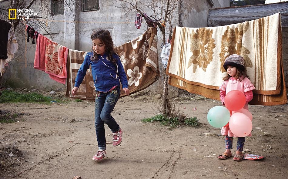 """تستمتع """"هبة فراس رحال"""" (10 أعوام) بلعبتها المفضلة """"الحجلة"""" أمام بيتها المؤقت، إذ تذكرها اللعبة بصديقاتها وحياتها في مدينة حلب."""