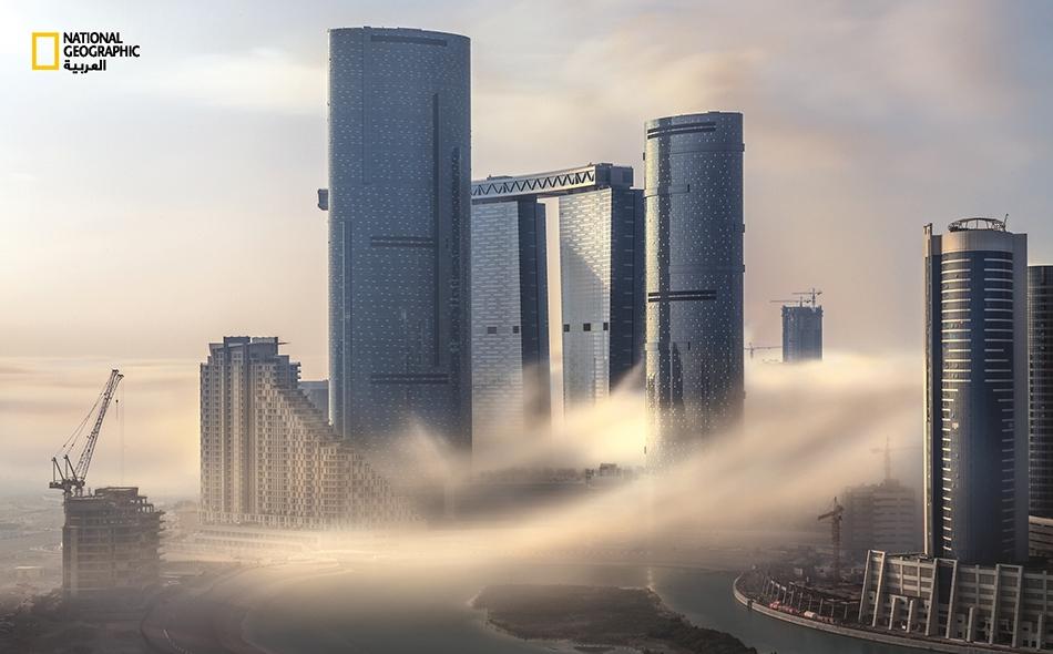 """موجة من الضباب تعبر بين الأبراج السكنية الشاهقة في جزيرة """"الريم"""". تتميز هذه الجزيرة ببناياتها متعددة الطوابق وتصاميمها العصرية الجذابة وأشهرها """"أبراج البوابة المتصلة""""."""