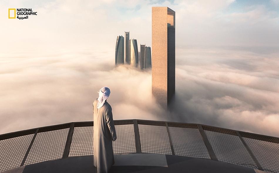"""يقف هذا الشاب متأملاً الضباب الكثيف وهو يحيط بمباني شركة """"أدنوك"""" و""""أبراج الاتحاد"""" في أبوظبي."""