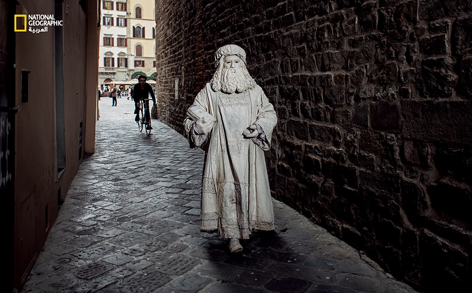 """في فلورنسا، اشتهر ليوناردو بموهبته المذهلة وتلقّى كذلك أولى طلبيّاته. يصفه الباحث """"باولو غالوتسي"""" بالقول: """"لقد كان زينةً ورمز قوّة لرعاته"""". في الصورة، فنّانُ شوارع إيطالي يدعى """"فالتر كونتي""""، متقمّصًا شخصية ليوناردو ذات المكانة المرموقة بين المشاهير؛..."""