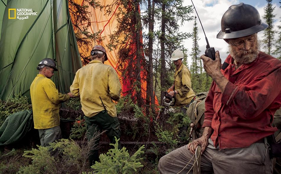 """يتواصل قائد العملية، """"تاي هامفري""""، مع طيّار ألقى معدات بالقرب من الحريق. يحرر أفراد الطاقم المظلة من شجرة في المكان الذي سقطت فيه الحمولة."""
