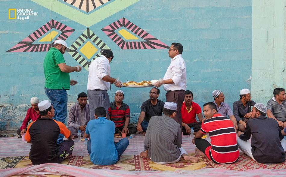 يحاول القائمون على هذه المائدة الرمضانية التعجيل بتهيئ الطعام قُبيل موعد أذان المغرب في إحدى مناطق مدينة المنامة بالبحرين. يساعد أفراد من ديانات أخرى هؤلاء الصائمين من خلال حمل الأطباق وتوزيعها عليهم.