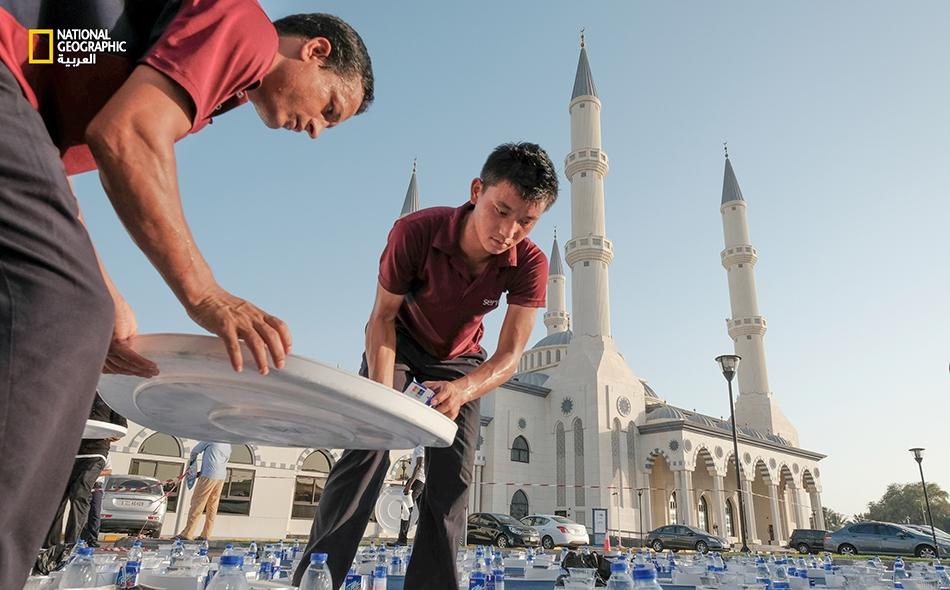 """متطوعان يقومان بترتيب الطعام على المائدة الرمضانية في الساحة الخارجية لدى مسجد """"الفاروق عمر بن الخطاب"""" بمنطقة """"جميرا"""" في دبي. يضم هذا المسجد مساحة داخلية وغرفة خاصة للنساء للإفطار، وما يميزه هو تنوع الوجبات المقدمة للصائمين طوال أيام شهر رمضان."""