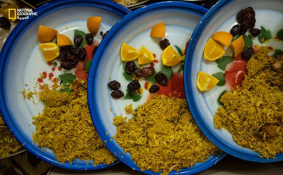 ثلاثة أطباق متشابهة تضم حبات من التمر والبرتقال وكمية من الأرز المطهو مع الدجاج، يُشكل كلٌّ منها الجزء الأعظم من وجبة إفطار لشخص من الصائمين.