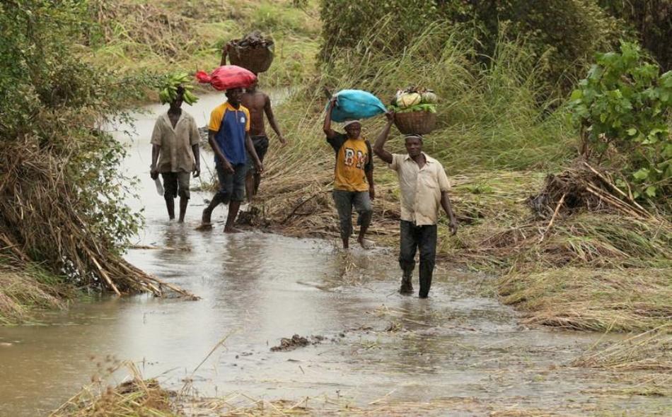 """قرويون يحملون الذرة وغيرها من المحاصيل من الحقول التي غمرتها المياه على رؤوسهم قرب مدينة بيمبا، بعدما ضربها الإعصار """"كينيث"""". الصورة: مايك هوتشينجز، رويترز."""