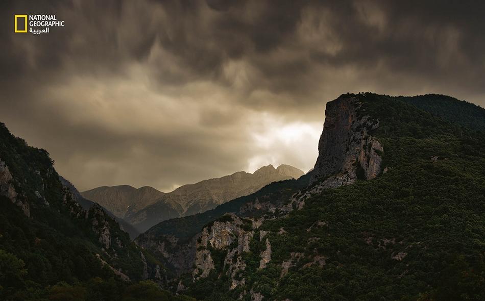 """تتربَّع على جبل """"أوليمبوس"""" قممٌ متعددة. اعتقد الإغريق القدامى أن قمة """"ميتيكاس"""" المسنَّنة (تظهر في الصورة تحت وهج عاصفة) كانت مقاما لأعظم الآلهة، بما فيها """"زيوس""""، إله قوى الطبيعة والرعد."""