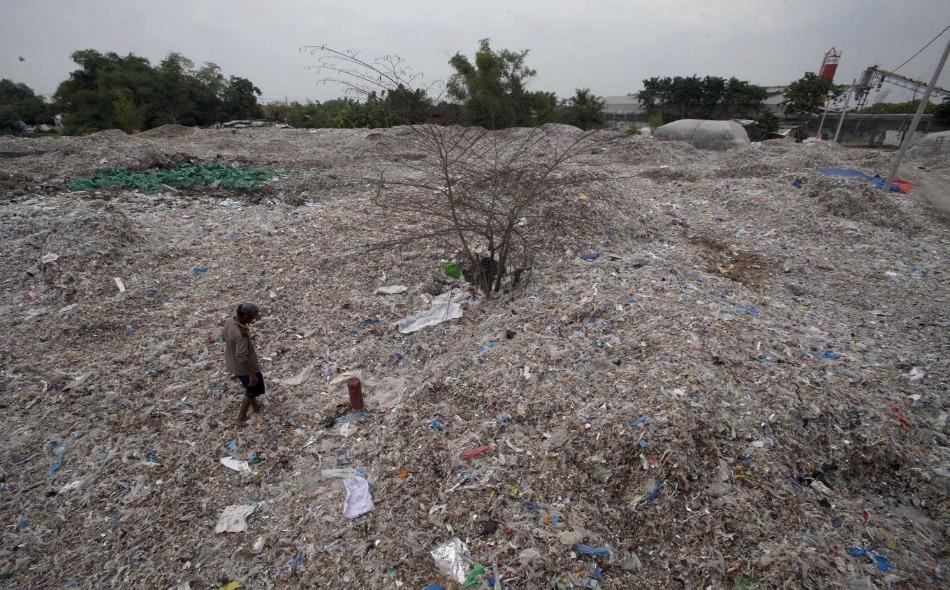 """في أفنية منازل قرية """"بانغون"""" الإندونيسية تتكدس النفايات على أرض كانت يزرع عليها الأرز يوما. ويبحث سكان هذه القرية بين الأكوام عن المواد المصنوعة من البلاستيك والألمنيوم لبيعها إلى شركات التدوير. الصورة: JP/Sigit Pamungkas"""