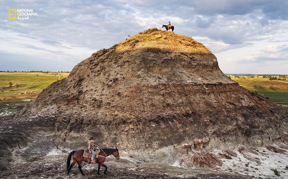 """يستكشف مربي الماشية """"كلايتون فيبس"""" (أعلى) المعروف في بعض الدوائر باسم """"راعي الديناصورات""""، جزءًا من تشكيل """"هيل كريك"""" بالقرب من منزله في بلدة """"جوردان"""" بولاية مونتانا، برفقة ابنه """"لوك"""". ويعود تاريخ طبقات هذه الصخرة الغنية بالحفريات إلى نهاية العصر..."""