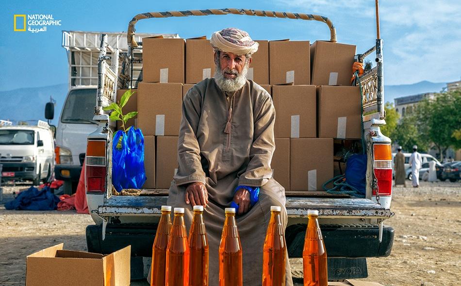 """يجلس هذا الرجل الخبير في ماء الورد لدى """"سوق الجمعة"""" بولاية نزوى، منتظرًا المشترين التواقين لاقتناء منتجه الزكي."""