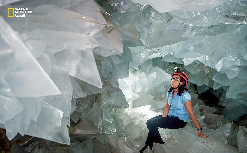 """تجلس عالمة الجيولوجيا """"ميلاغروس كاريتيرو"""" داخل """"حجر جيود بالبي""""، وهو أحد أكبر أحجار الجيود في العالم."""